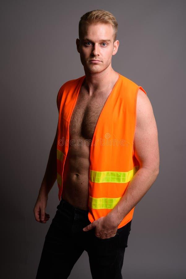 Молодой красивый рабочий-строитель человека без рубашки против серого ба стоковые изображения rf