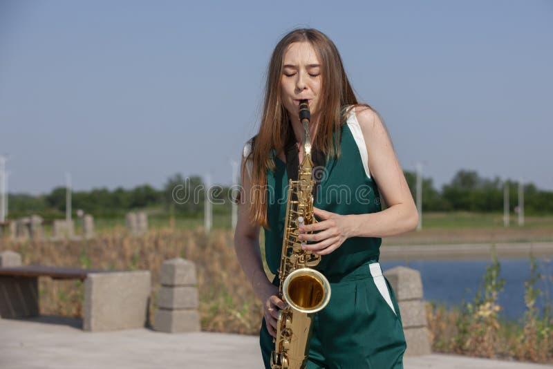 Молодой красивый саксофонист с саксофоном - на открытом воздухе в природе стоковые изображения rf