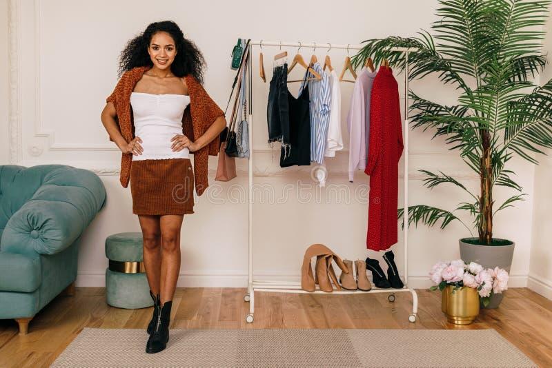 Молодой красивый стилизатор показывая ее шкаф стоковая фотография
