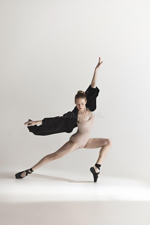 Молодой красивый танцор в бежевых танцах купальника на серой предпосылке стоковое фото