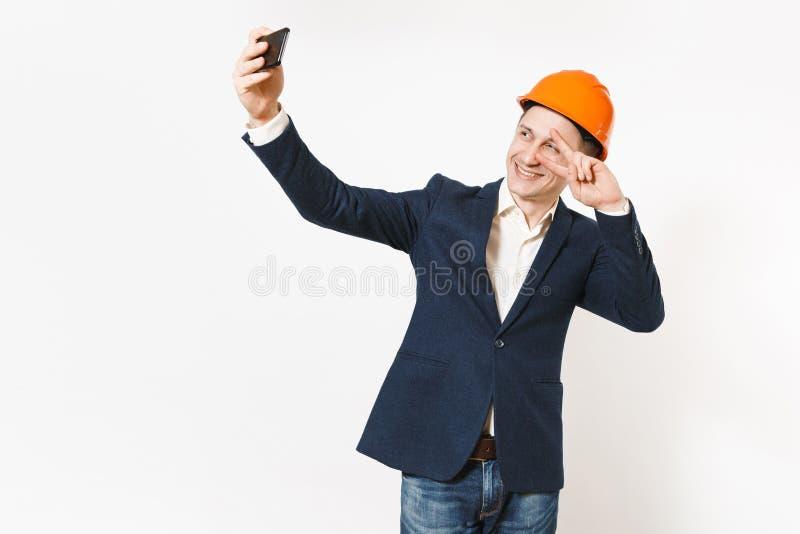 Молодой красивый усмехаясь бизнесмен в темном костюме, защитном знаке победы показа защитного шлема и selfie делать на черни стоковые фото