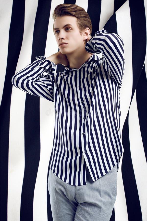 Молодой красивый человек в представлениях striped рубашки на черно-белую предпосылку стоковые фотографии rf
