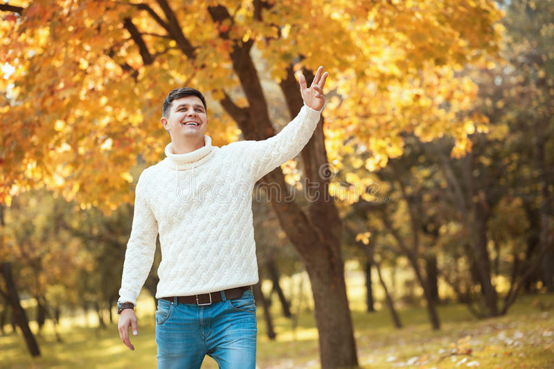 Молодой красивый человек в свитере и джинсах оставаясь в парке осени оранжевом усмехаясь и развевая к кто-то стоковая фотография