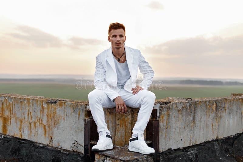 Молодой красивый человек в стильный белый сидеть одежд стоковое фото