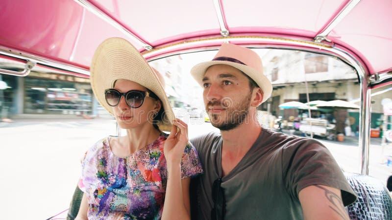 Молодой красивый человек в шляпе с его ездой подруги на традиционном тайском songteo шины Перемещение Таиланд пар во время их стоковое изображение