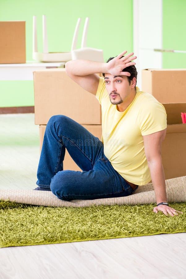 Молодой красивый человек двигая внутри к новому дому с коробками стоковые изображения