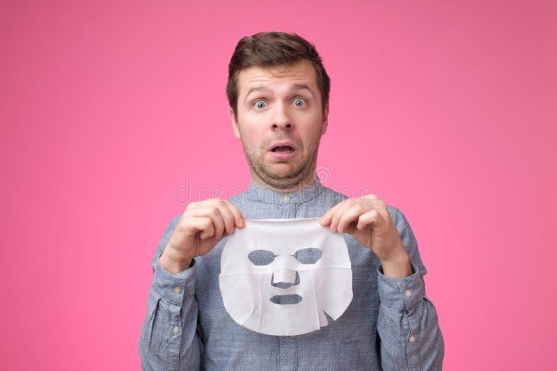 Молодой красивый человек держа косметическую маску и смотря озадаченное положение на розовой предпосылке стоковые изображения