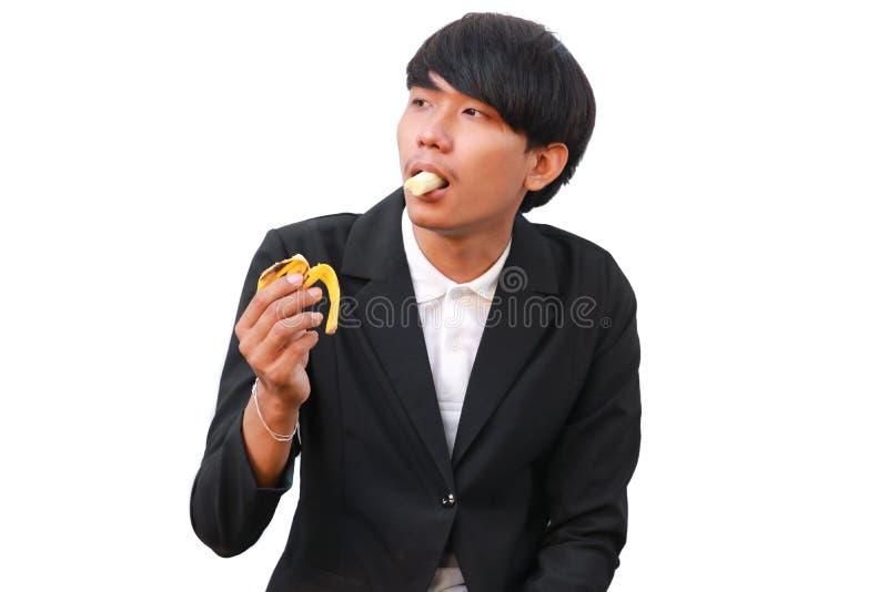 Молодой красивый человек есть банан на белой предпосылке стоковое фото rf