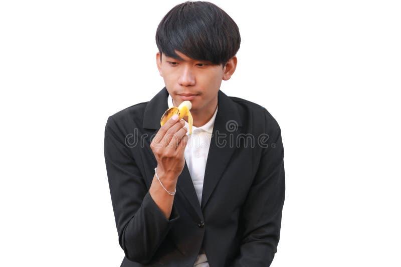 Молодой красивый человек есть банан на белой предпосылке стоковые изображения rf
