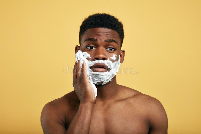 Молодой красивый человек имея проблемы с кожей во время брить его бороду стоковая фотография rf