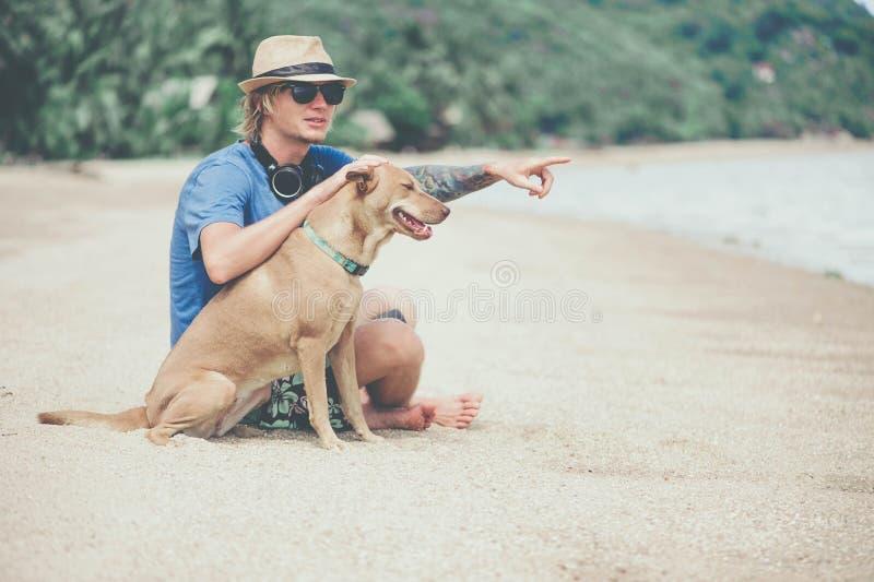 Молодой красивый человек нося голубые футболку, шляпу и солнечные очки, сидя на пляже с собакой стоковые фотографии rf