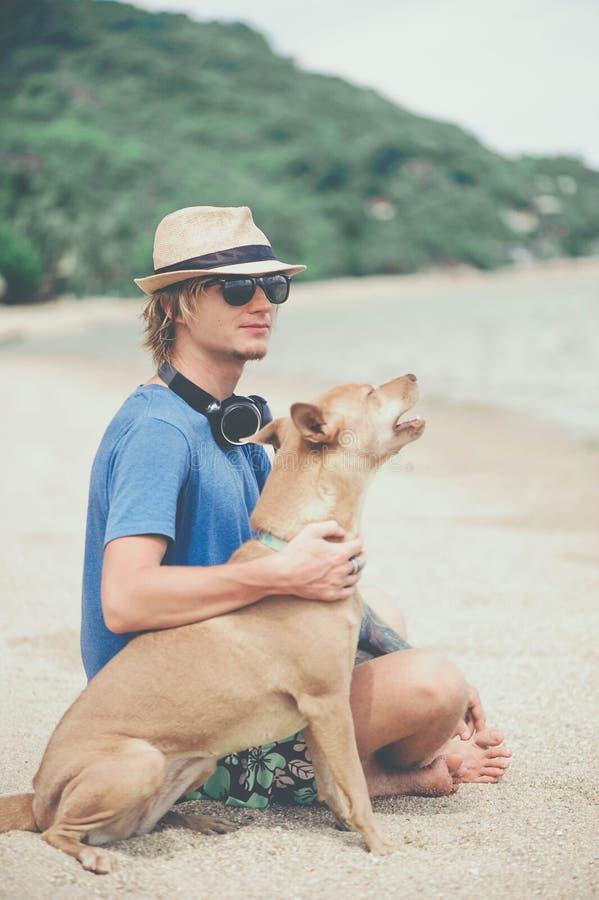 Молодой красивый человек нося голубые футболку, шляпу и солнечные очки, сидя на пляже с собакой в Таиланде стоковые изображения rf