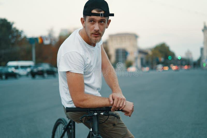 Молодой, красивый человек представляя пока сидящ на велосипеде, на дороге города стоковое фото rf