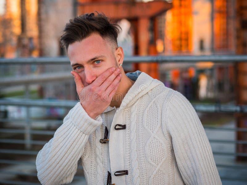 Молодой красивый человек пробуя не смеяться стоковые изображения rf