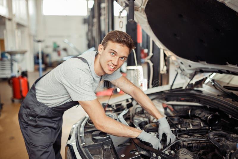 Молодой красивый человек проверяет двигатель автомобиля на обслуживании автомобиля стоковая фотография rf