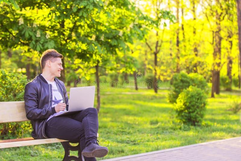 Молодой красивый человек сидящ и работающ в парке с компьтер-книжкой Фрилансер парня работает снаружи и улыбка стоковое фото