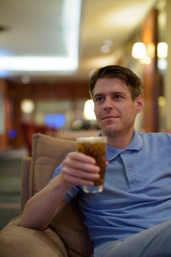 Молодой красивый человек сидя и ослабляя на лобби гостиницы стоковое фото
