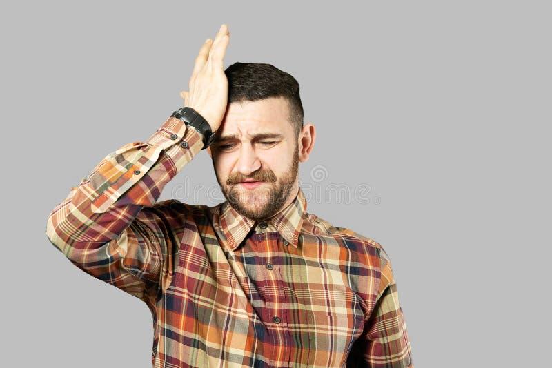 Подходящий молодой человек представляя над серой предпосылкой стоковое фото rf