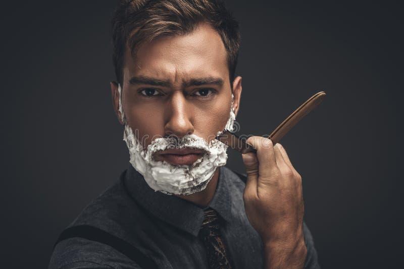 Молодой красивый человек с кремом для бритья на его стороне, холя его бороду с прямой бритвой и смотреть стоковая фотография rf