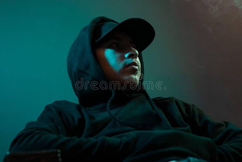 Молодой крутой рэппер с черным hoodie и крышкой выглядя косой стоковое фото rf