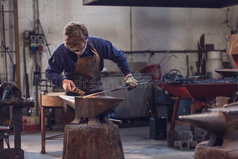 Молодой кузнец работая с накаленным докрасна металлом стоковые фото