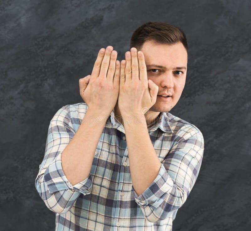 Молодой любознательный человек peeking через ладони стоковые изображения