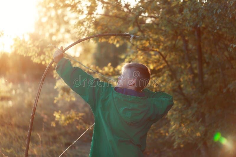 Молодой мальчик, всход с handmade луком и стрелы на цели на заходе солнца, outdoors летнего времени стоковые фотографии rf
