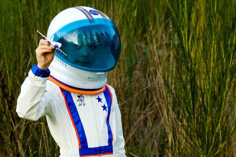 Молодой мальчик в плоскости игрушки летания костюма астронавта стоковые фотографии rf