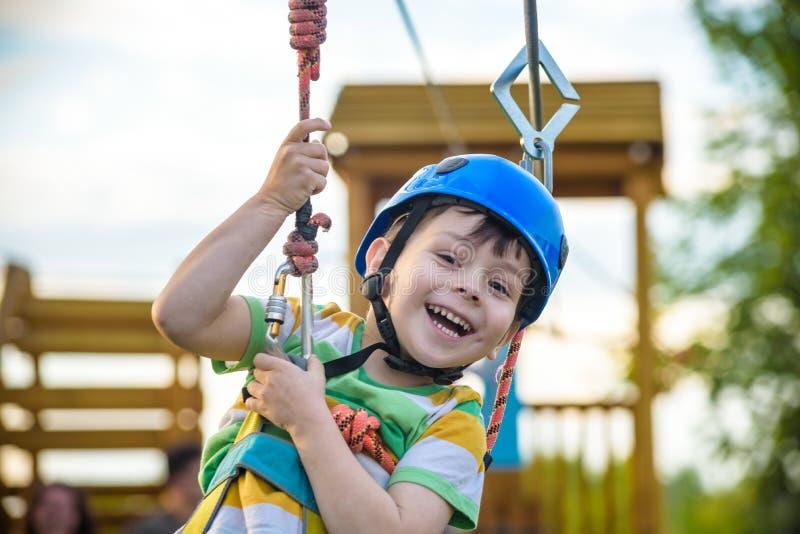 Молодой мальчик играя и имея потеху делая деятельность outdoors Happ стоковые фотографии rf