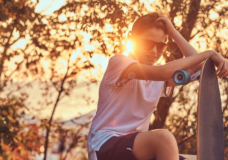 Молодой мальчик конькобежца в солнечных очках одел в футболке и шортах сидя на каменном усовике outdoors на заходе солнца стоковая фотография