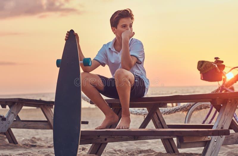 Молодой мальчик конькобежца одел в футболке и шортах сидя на стенде на фоне берега моря на яркой стоковое изображение rf