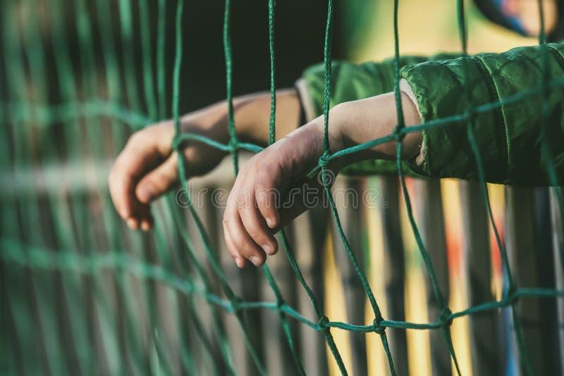 Молодой мальчик наблюдает игру спорт от места на открытой трибуне с футболом стоковые фотографии rf