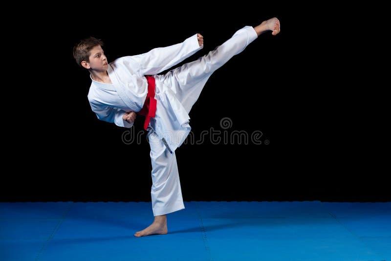 Молодой мальчик одел в белом кимоно карате с красным поясом стоковое изображение rf
