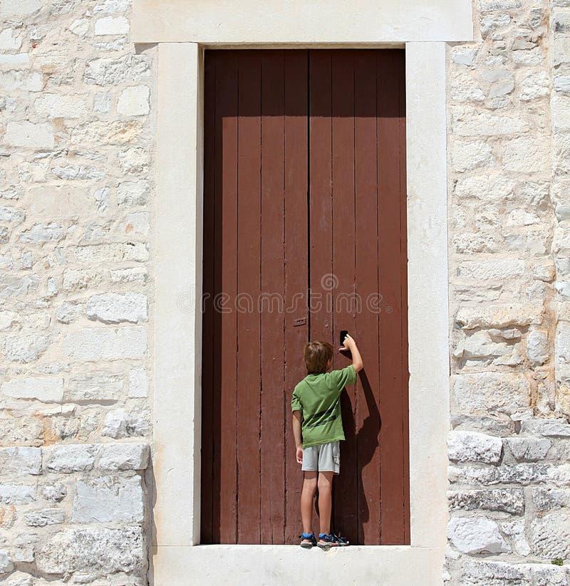 Молодой мальчик перед большой дверью стоковые изображения rf