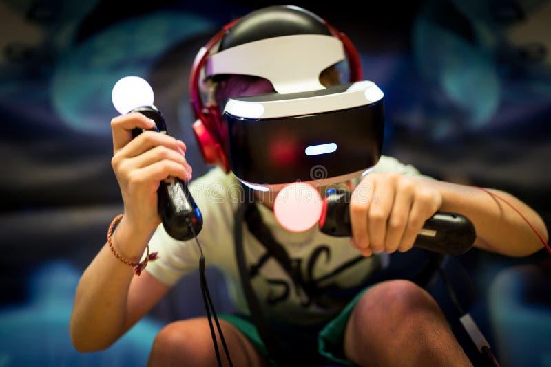 Молодой мальчик подростка используя шлемофон виртуальной реальности с изумленными взглядами и руки жестикулируют регуляторы в игр стоковые фотографии rf