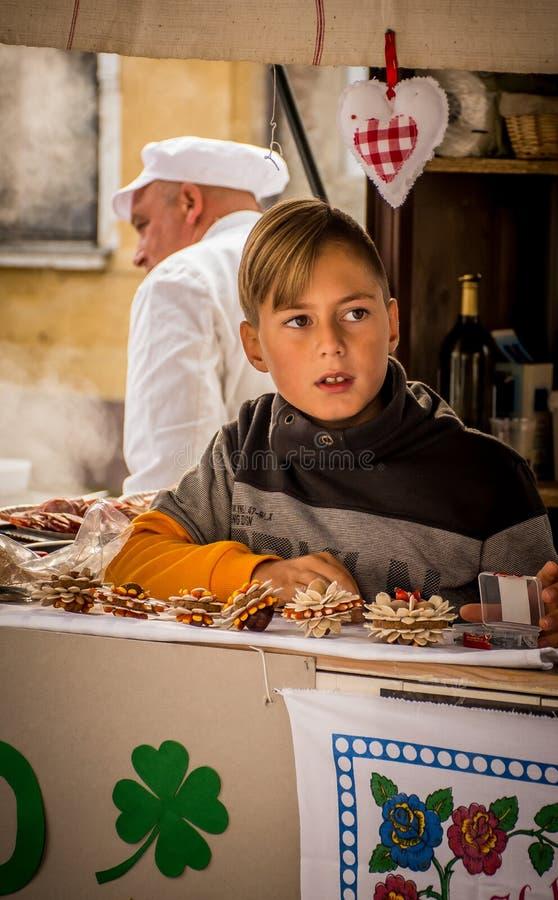 Молодой мальчик представляя традиционную еду на праздненствах городка стоковые изображения rf