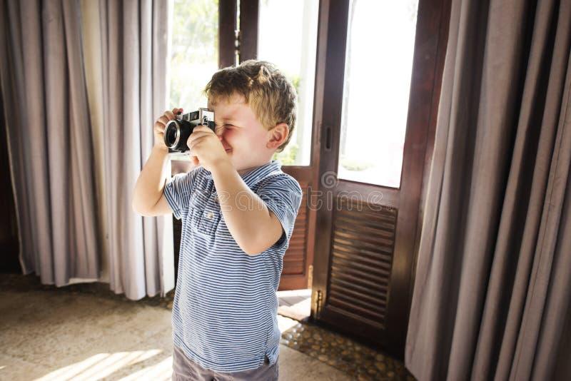 Молодой мальчик принимая фото с винтажной камерой фильма стоковая фотография rf