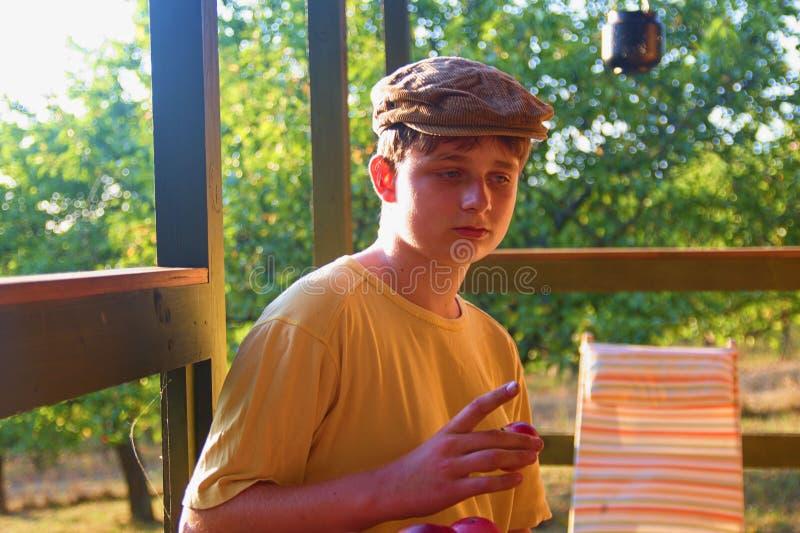 Молодой мальчик сидит на verandah и eatting свежих яблоках Мечтательное и романтичное изображение Лето и счастливое детство стоковое изображение