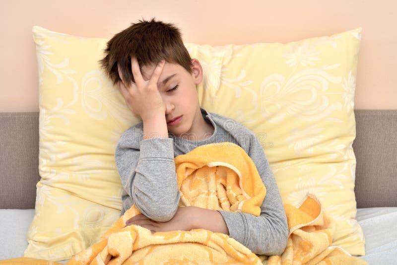 Молодой мальчик сидя в кровати с головной болью стоковые изображения