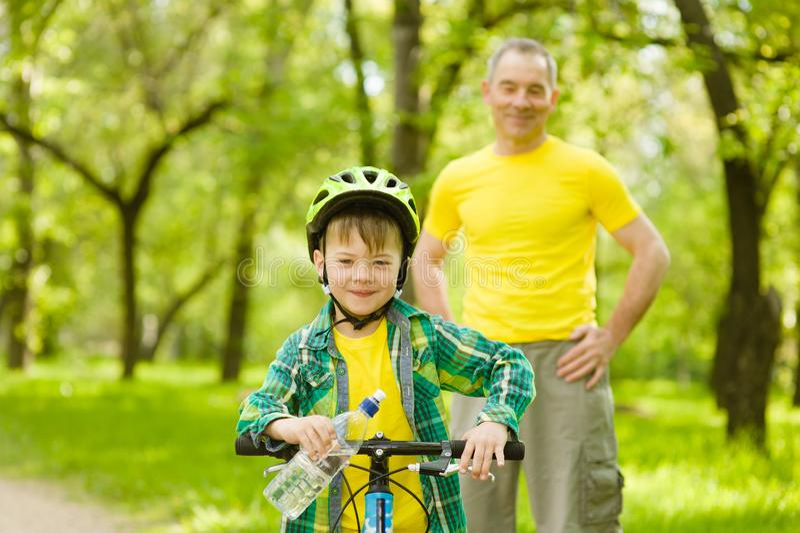 Молодой мальчик с бутылкой воды учит ехать велосипед с его дедом стоковое фото rf