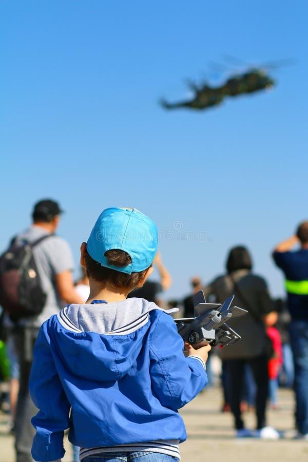 Молодой мальчик с самолетом игрушки в руке восхищая румынские вертолеты пумы военновоздушной силы IAR 330 выполняя показательный  стоковая фотография rf