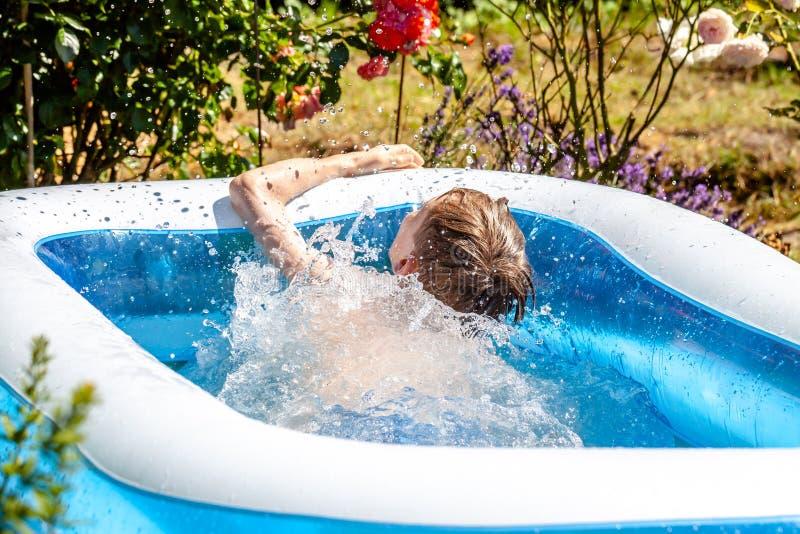 Молодой мальчик тонуть в бассейне летом стоковое фото