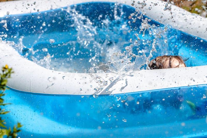 Молодой мальчик тонуть в бассейне летом стоковые изображения rf