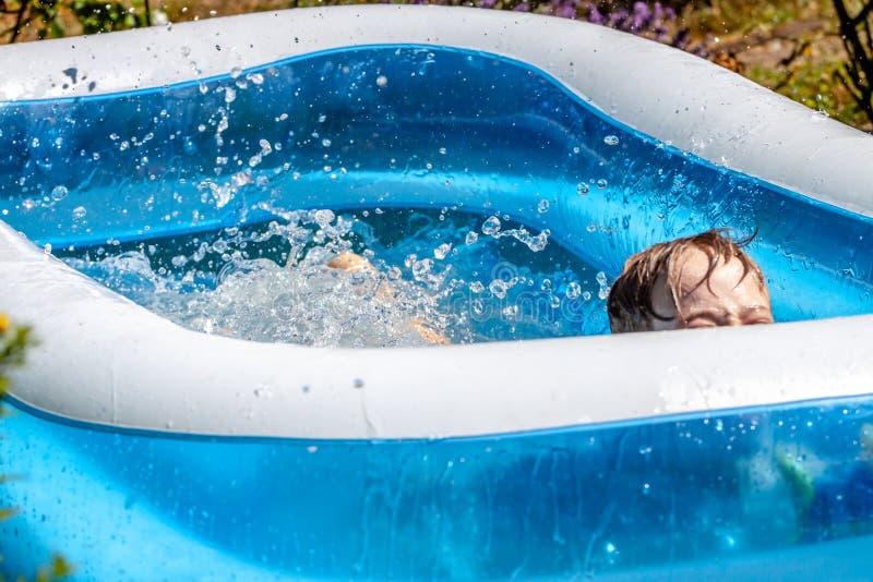 Молодой мальчик тонуть в бассейне летом стоковое изображение