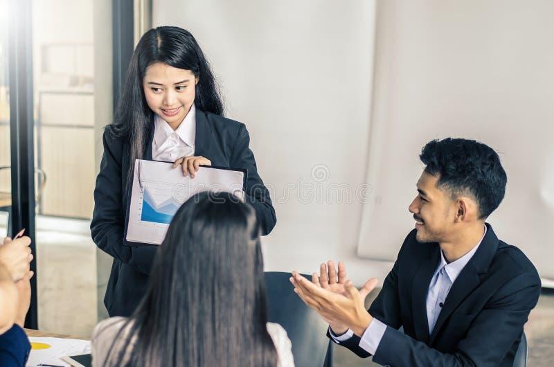 Молодой менеджер стоя делающ представлением финансовую диаграмму пока другие слушая к ей стоковые фотографии rf