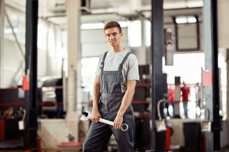 Молодой механик автомобиля стоит с универсальным гаечным ключом в его руках стоковое изображение rf