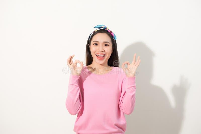 Молодой милый азиатский знак ОК показа женщины с 2 руками r на белой предпосылке стоковые фото