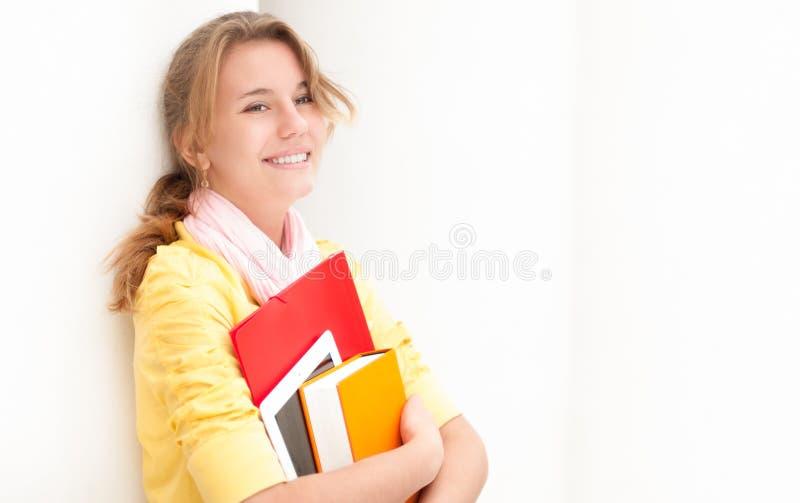 Молодой милый женский студент на белой предпосылке. стоковая фотография