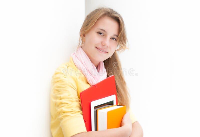 Молодой милый женский студент на белой предпосылке. стоковые фото