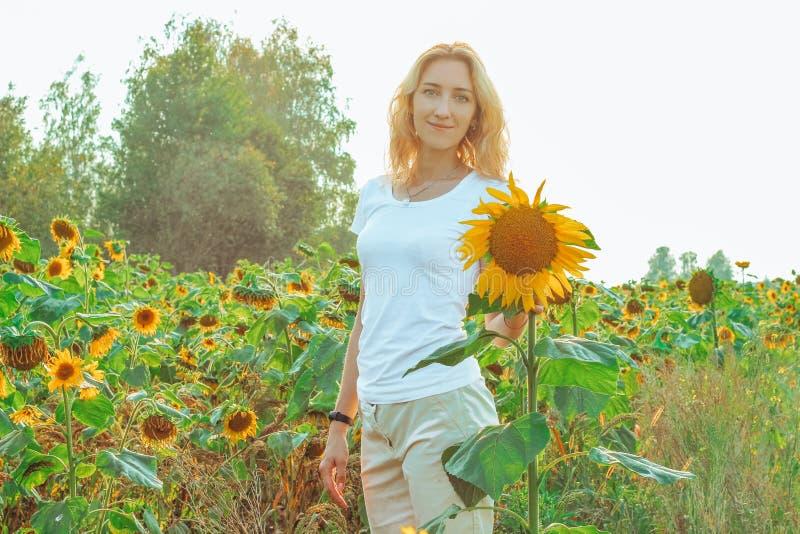 Молодой милый крупный план женщины с солнцецветом на предпосылке поля на летнем времени стоковое фото rf
